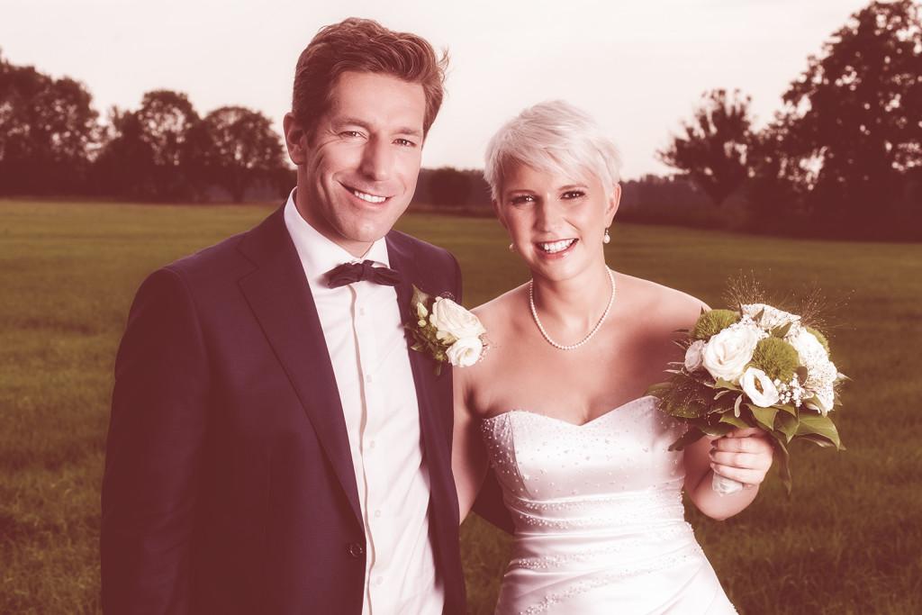 Hochzeitsfoto mit dem Brautpaar auf einer Wiese im Vintage Look