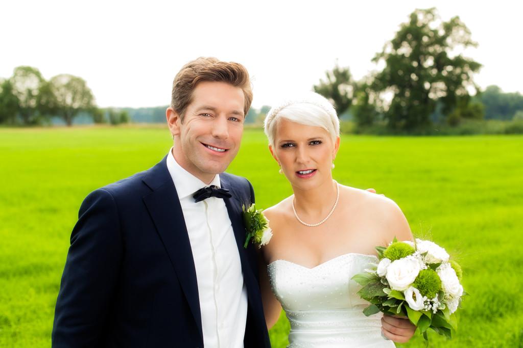 Hochzeitsfoto mit dem Brautpaar auf einer Wiese